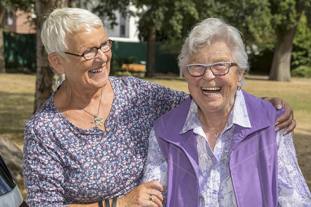 zwei lachende ältere Damen (Betreuerin u. Betreute)