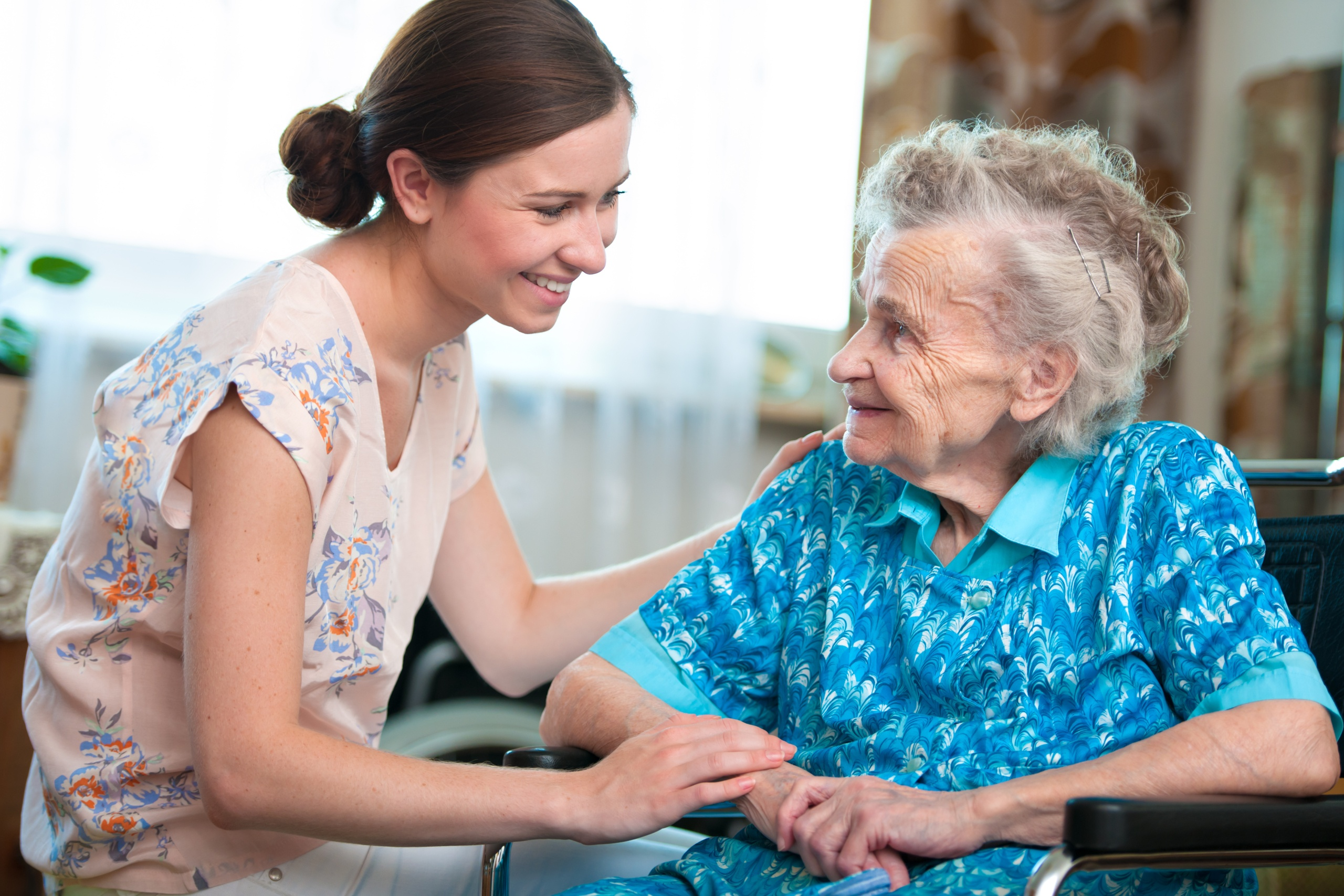 Seniorin bekommt häusliche Zuwendung von junger Frau